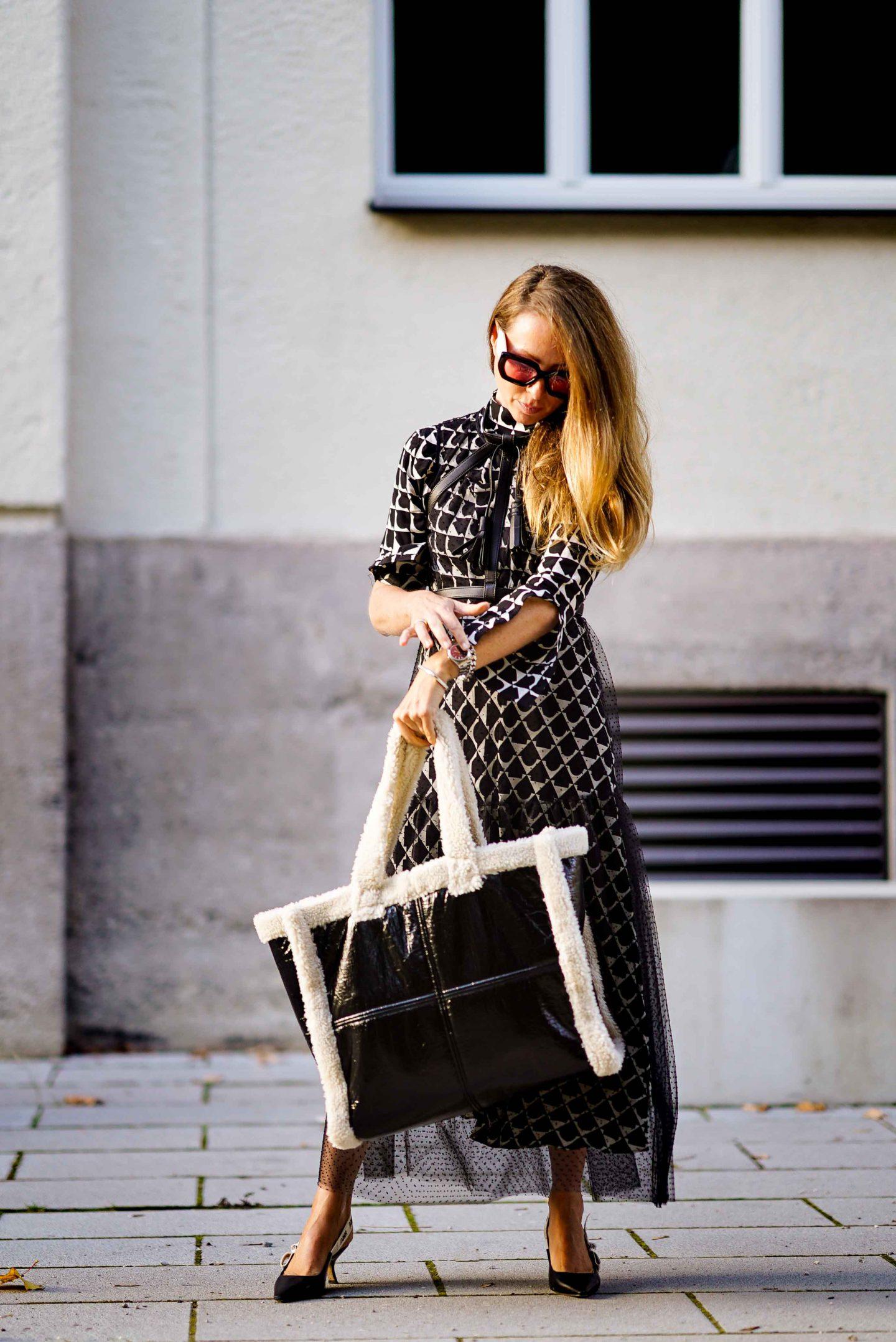 Fashion Bloggerin Nicki Nowicki mit dem Taschen Trend der Saison: Stand Studio Bag aus schwarzem Lack und Fake Fur